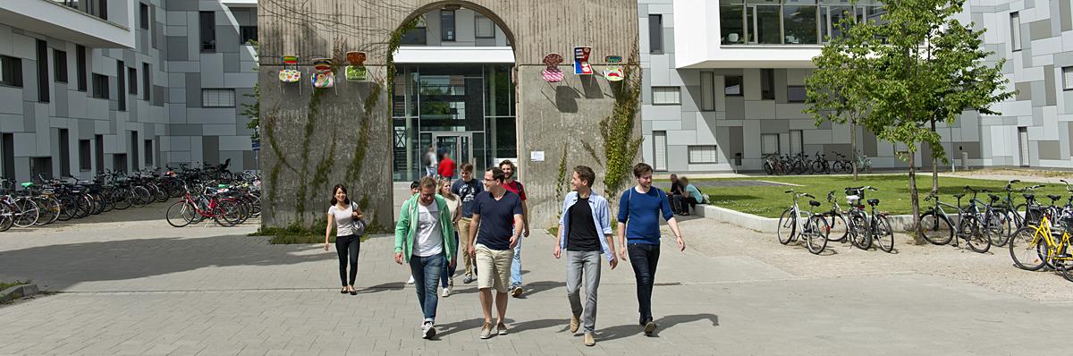 Gruppe Studierender vor Reitstalltor und LSG