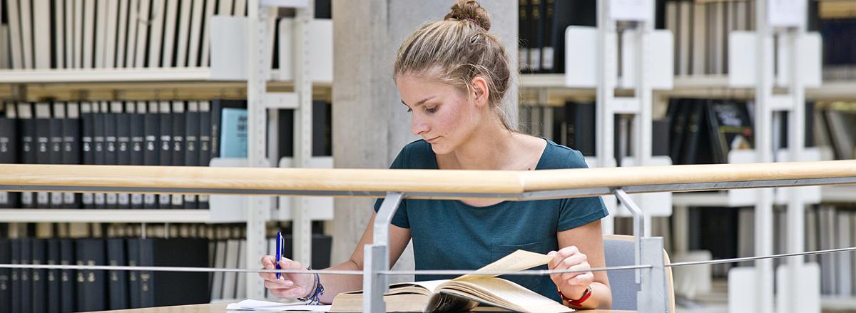 Studentin schreibend am Tisch in SUB