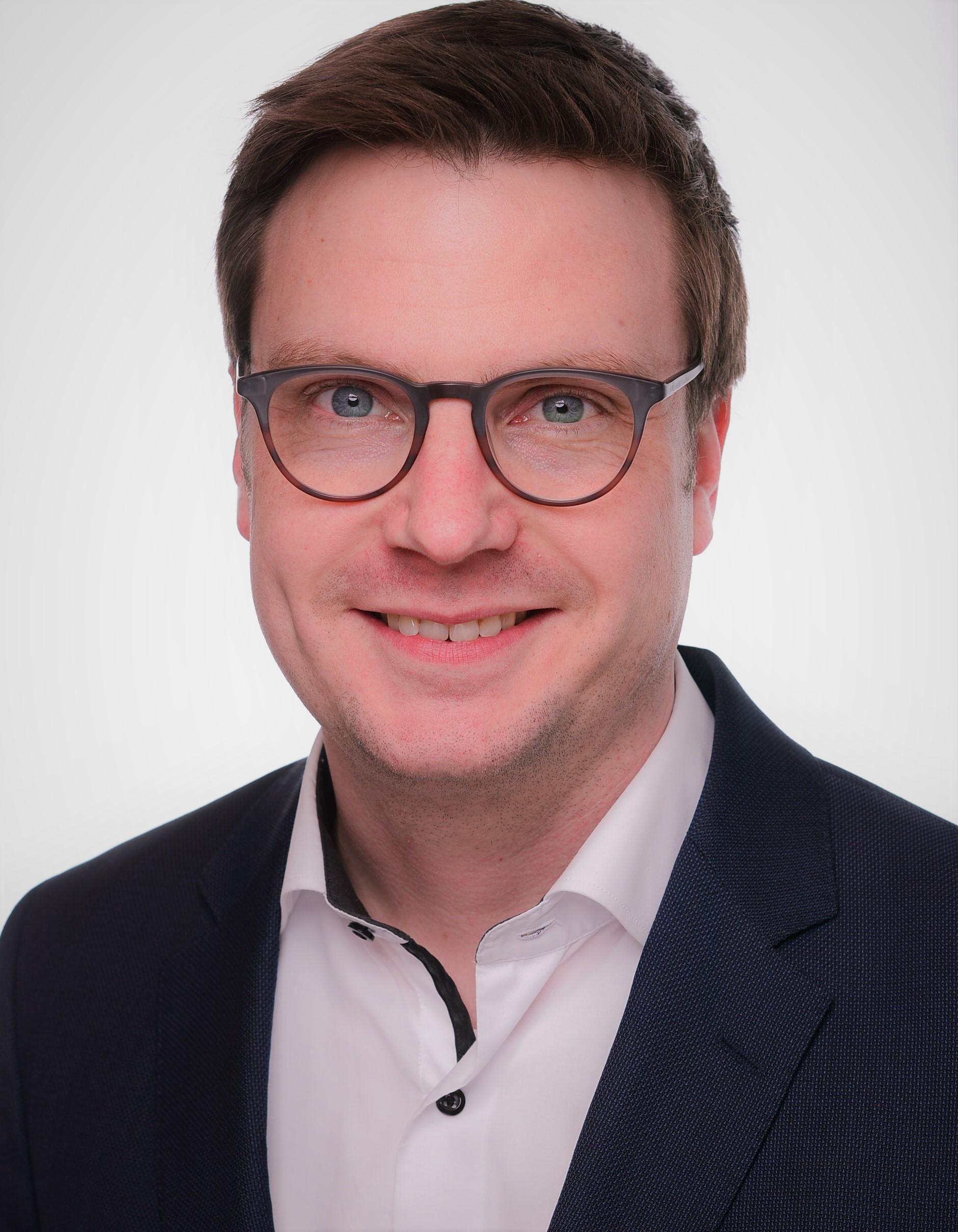 Porträtfoto von Björn Korte. Er trägt ein dunkles Jacket und ein weißes Hemd.