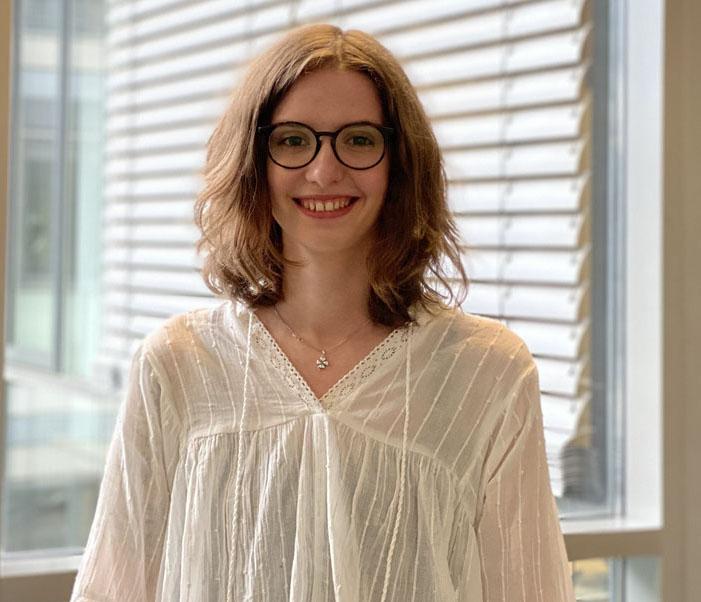 Porträtaufnahme von Lisa Weimer. Sie trägt eine weiße Bluse.