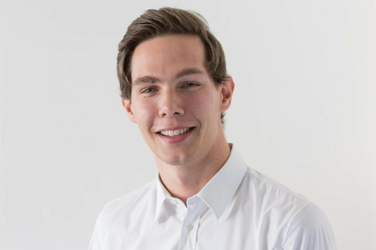 Porträtfoto von Lukas Tatge. Er trägt ein weißes Hemd.