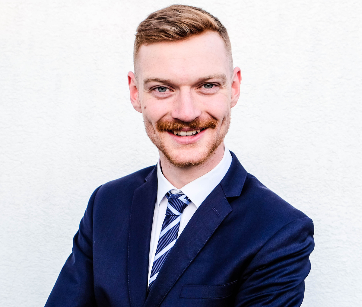 Porträtfoto von Kay Tuschen vor einer weißen Wand. Er trägt ein blaues Sakko und ein weißes Hemd mit blau-weiß-gestreifter Krawatte.