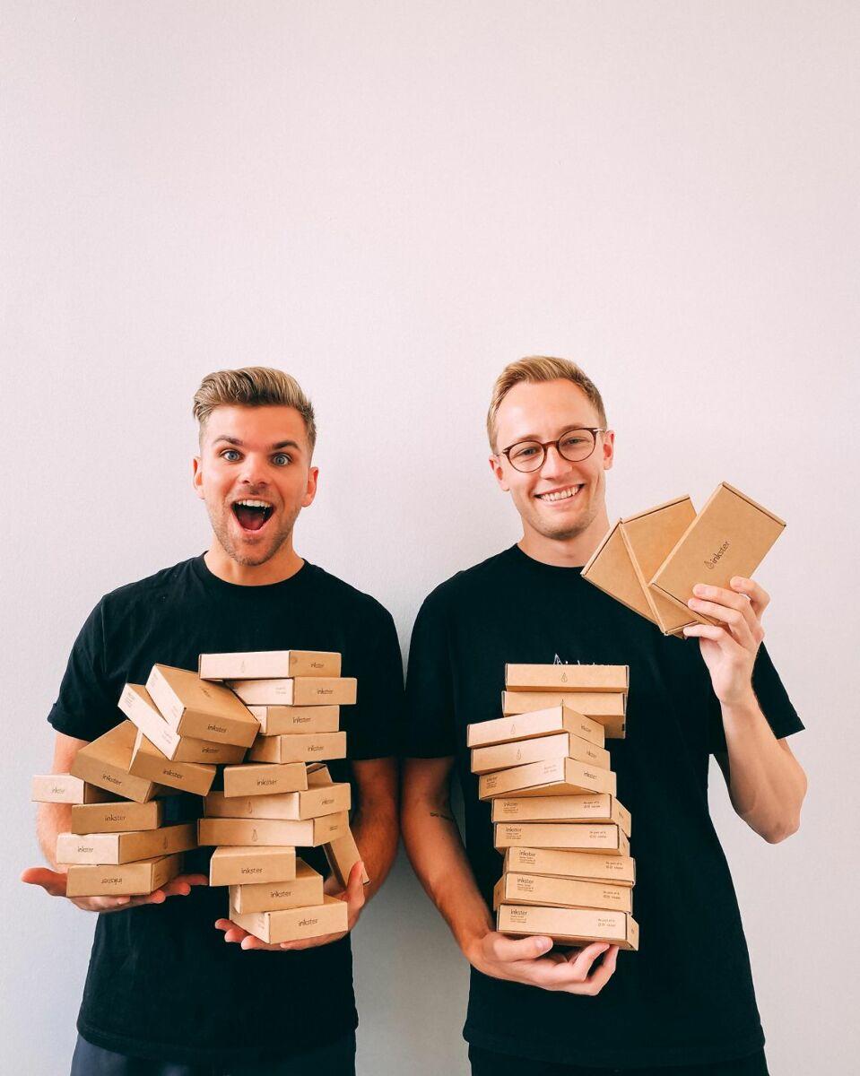 Melvyn Wittwer (links) und Michael Noack stehen nebeneinander und halten jeder einen Stapel brauner kleiner Kartons im Arm.