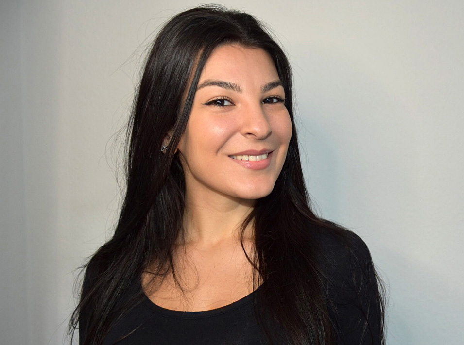 Porträtaufnahme von Anisa Buzani vor einer grauen Wand. Sie trägt ein schwarzes Langarm-Shirt.