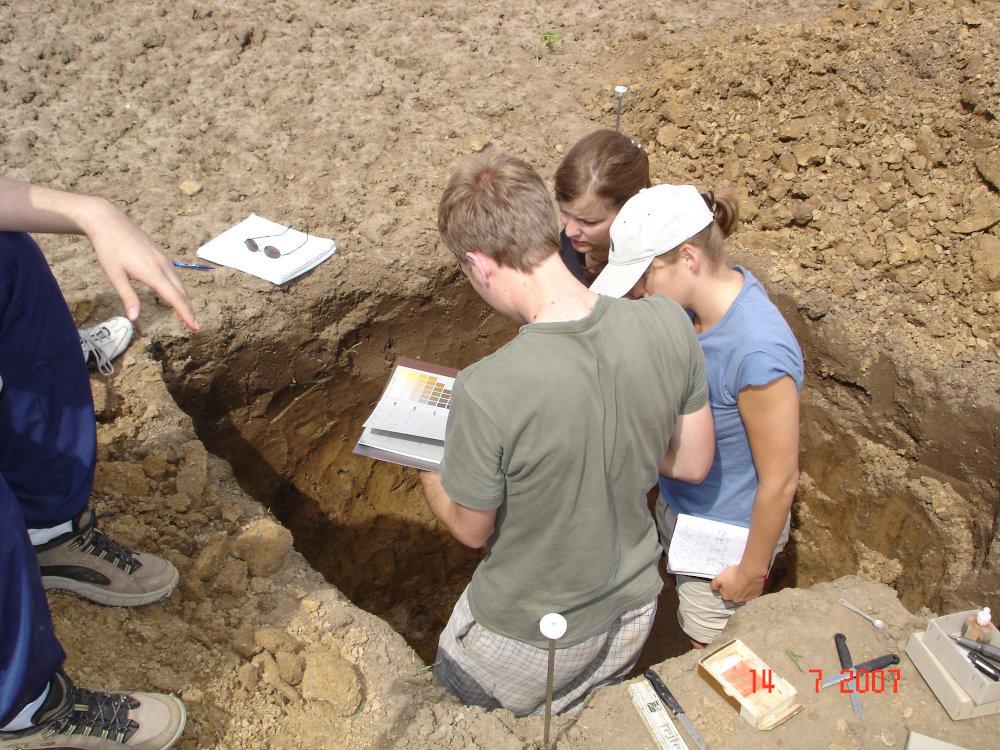 Mit dem Bachelor Geographie im Geländearbeiten - Studierende untersuchen einen Bodenaufschluss