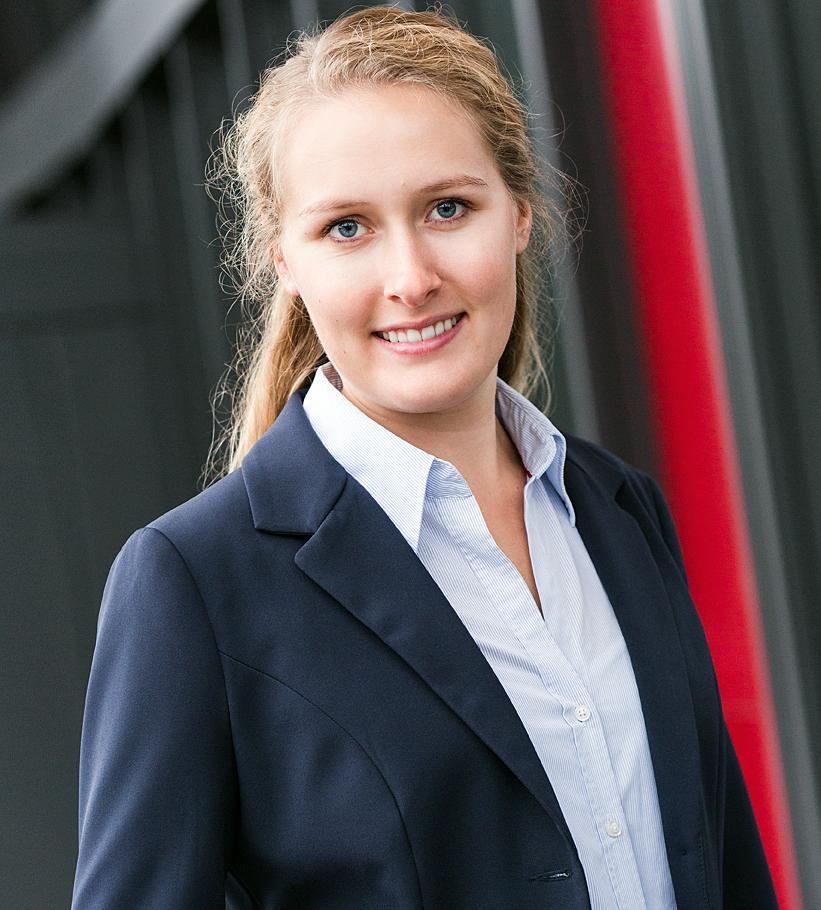 Porträtfoto von Annika Burneleit. Sie trägt einen dunkelblauen Blazer und eine hellblaue Bluse.