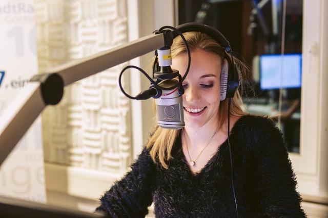Porträtfoto von Rebecca Claude. Sie sitzt im Radiostudio am Mikrofon und trägt Kopfhörer.