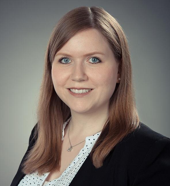 Porträtfoto von Katharina Althoff. Sie trägt einen schwarzen Blazer und eine weiße Bluse mit schwarzen Punkten.